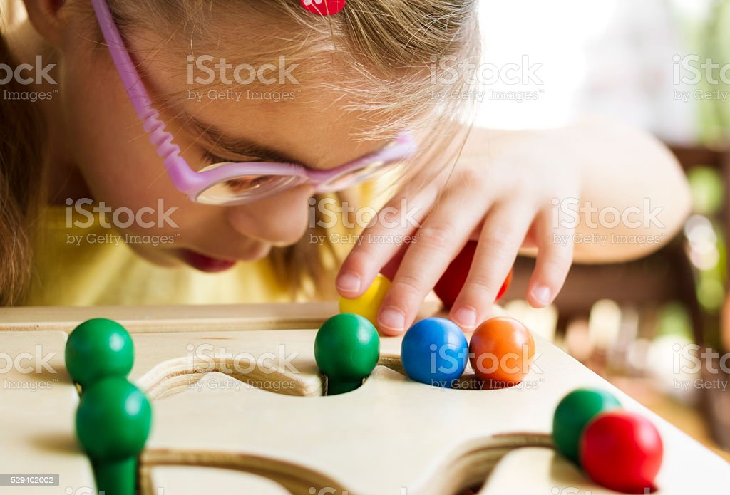 Visually disabled child with glasses playing with wooden pathfinder toy stock photo