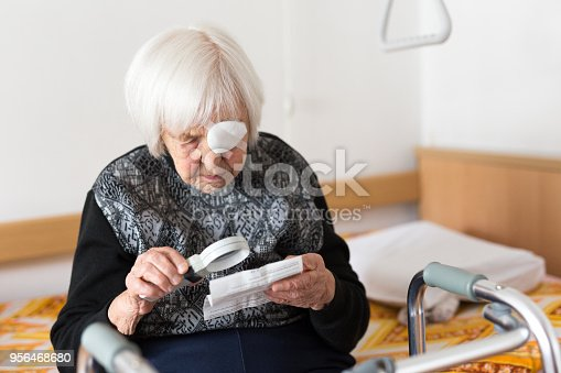 istock Visually impaired elderly 95 years old woman sitting at the bad trying to read with magnifying glass. 956468680