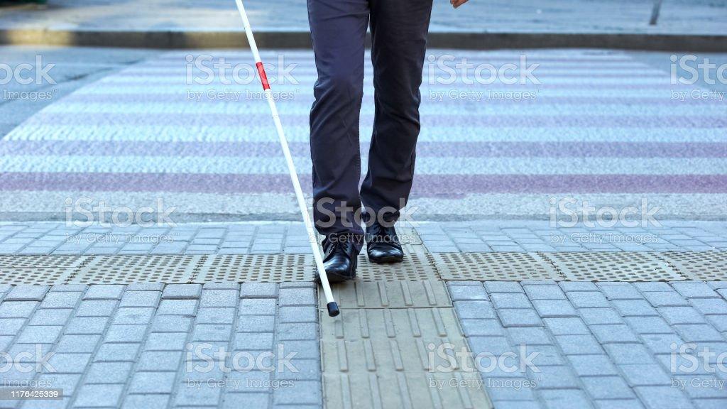 Sehbehinderter Mann mit taktilen Fliesen, um Stadt zu navigieren, Die Kreuzung zu beenden - Lizenzfrei Andersfähigkeiten Stock-Foto