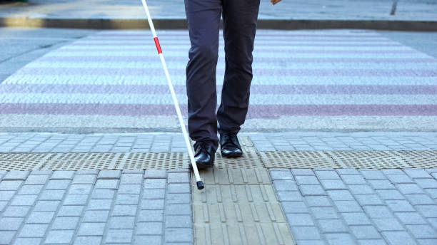 Visually impaired man using tactile tiles to navigate city, finishing crossroad stock photo