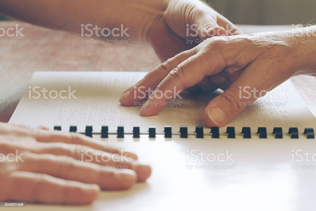 Visually impaired old person learning to reading by touch. stock photo