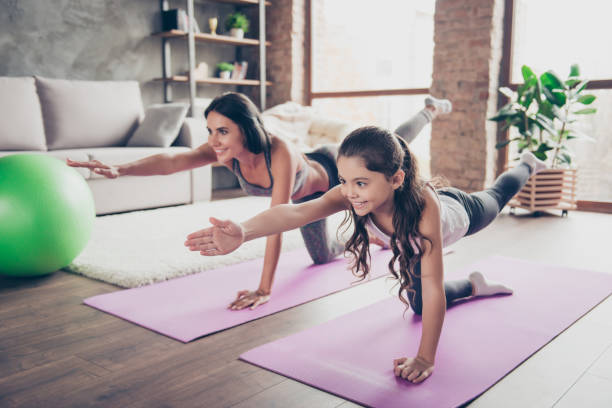 vitality concept. watch repeat the moves, poses from the helpful video! cute sweet cheerful joyful with long hair schoolgirl and slim sportive mom are doing stretching exercises in room om purple mats - ćwiczenie relaksacyjne zdjęcia i obrazy z banku zdjęć