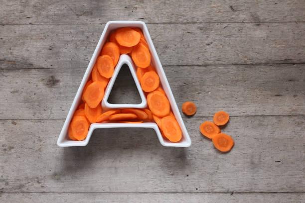 vitamina a en concepto de alimentos. placa en forma de la letra a con zanahorias frescas en rodajas en el fondo de madera. la endecha plana. - vitamina a fotografías e imágenes de stock