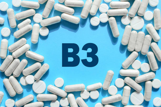 Vitamin B3 text in white capsules frame on blue background. Pill with Niacin. Dietary supplements and medication stock photo
