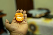 Vitamin C, a man hand holding a half portion of orange