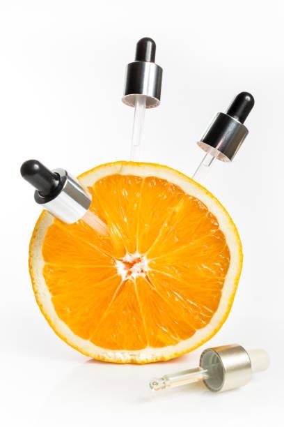 vitamine c in de vorm van serum in pipetten, ontleend aan een oranje voor jeugdige huid. - vitamine c stockfoto's en -beelden