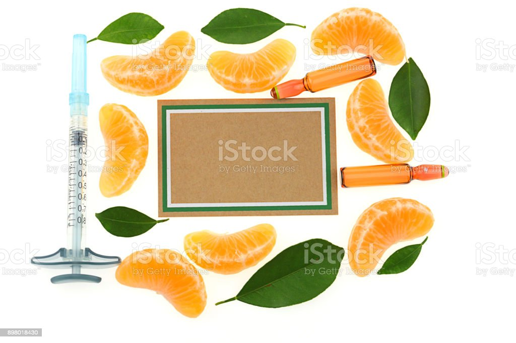 vitamin C Mock up. ampoules with vitamin C, syringe, slices mandarin and brown paper board on white background. Serum with Vitamin C stock photo