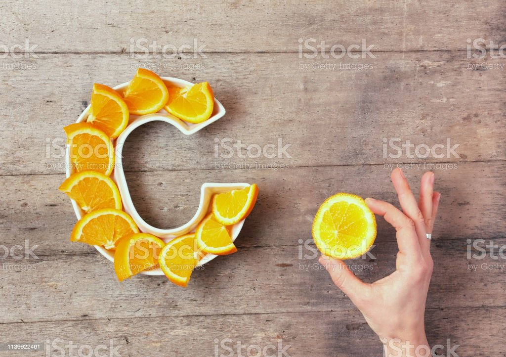Vitamin C or Ascorbic acid nutrient in food concept. Plate in shape of letter C with orange slices and woman's hand with citrus making sign OK on wooden background. Flat lay or top view. - Foto stock royalty-free di Acido