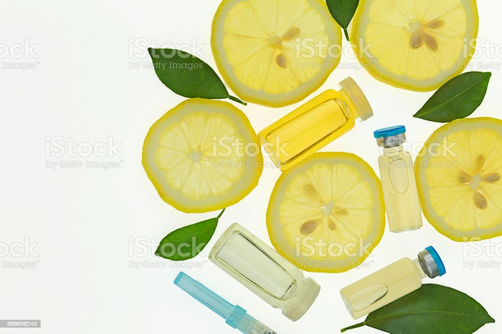Vitamin C. Serum with Vitamin C, ampoule, syringe, lemon slices and lemon leaves. biorevitalization and mesotherapy cocktail. Organic Natural Cosmetics Concept stock photo