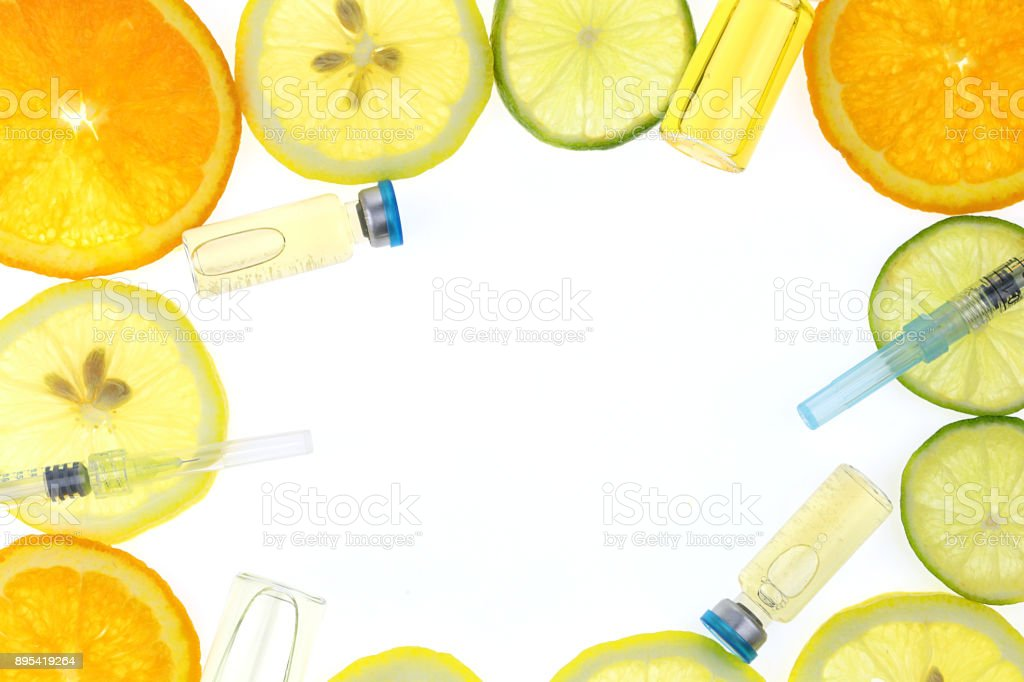 Vitamin C. Serum with Vitamin C. Frame of ampoules , syringe, orange, lime, lemon in a cut on a white background. Health Mockup stock photo