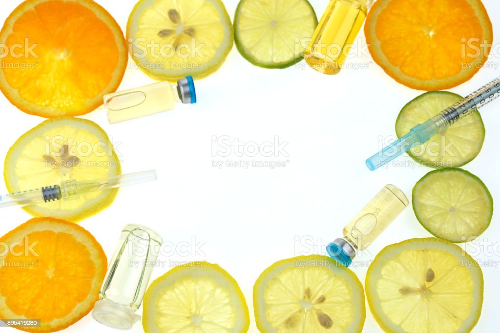 Vitamin C. Serum with Vitamin C. Frame of ampoules , syringe, orange, lime, lemon in a cut on a white background. Health and beauty Mockup stock photo