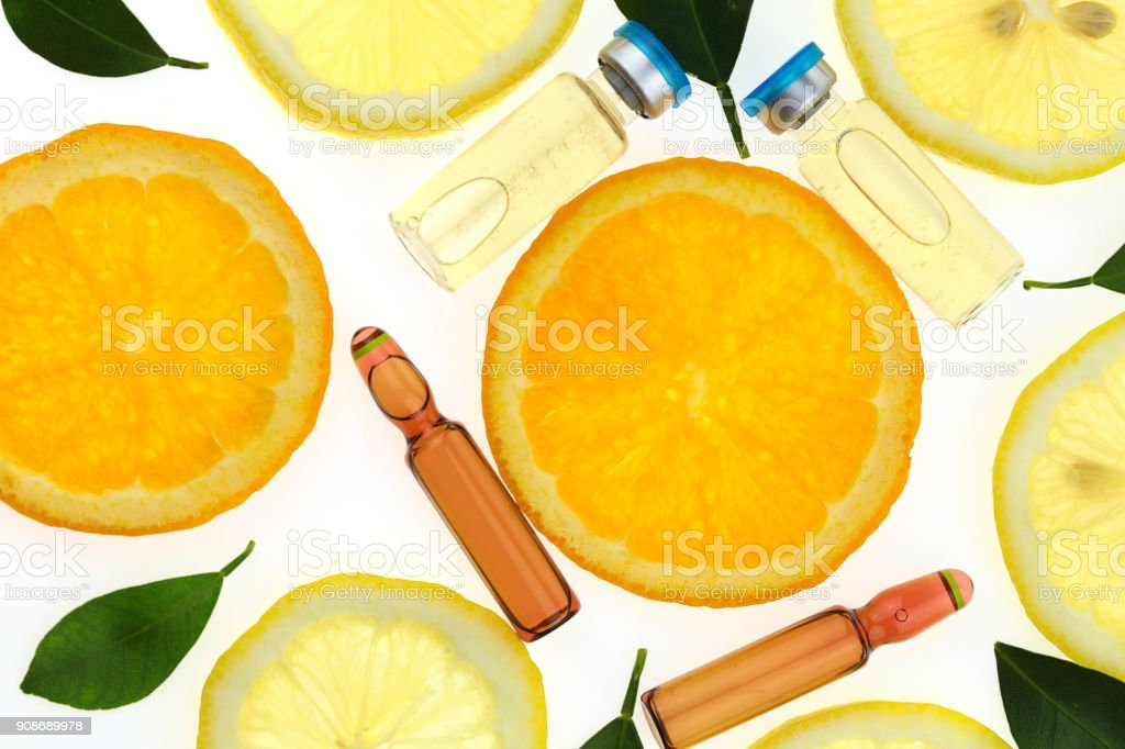 Vitamin C.ampoules with vitamin c and pieces of citrus fruit . Health and Beauty stock photo