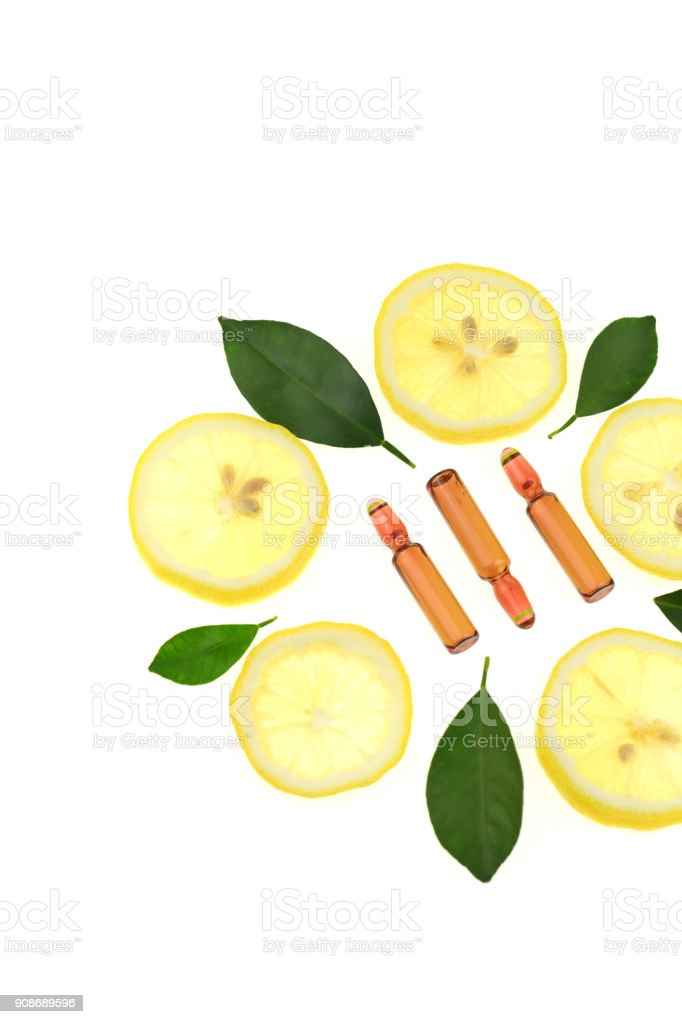 Vitamin C.ampoules with vitamin c and pieces of citrus fruit on a white background. Health and Beauty stock photo