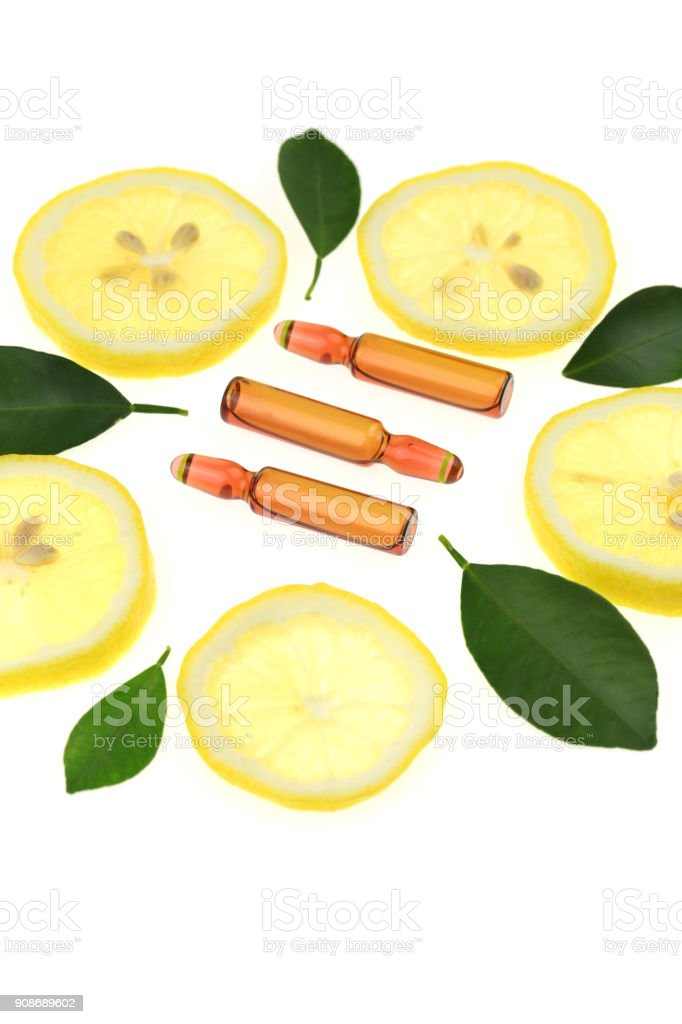 Vitamin C.ampoules with vitamin c and pieces of citrus fruit on a white background. Health stock photo