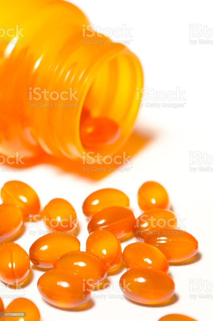Vitamin Capsules Spilling Out Of Pill Bottle royalty-free stock photo
