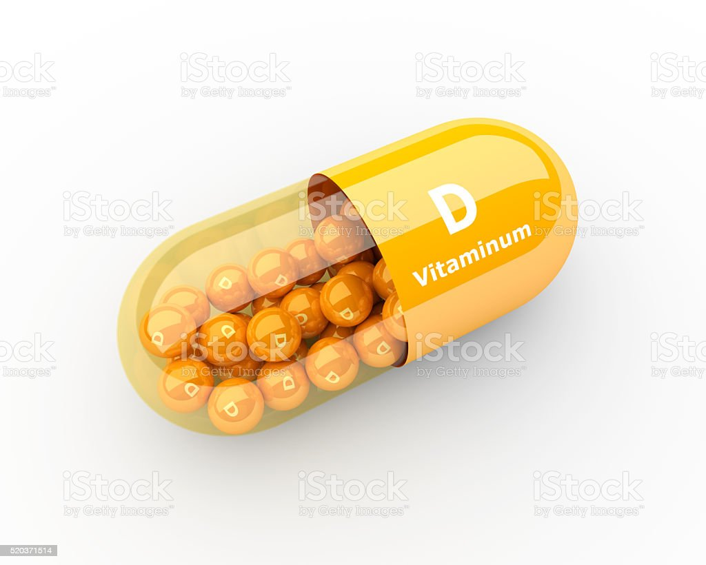 vitamin D capsule lying on desk stock photo