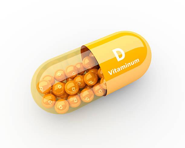 vitamin D capsule lying on desk stock photo