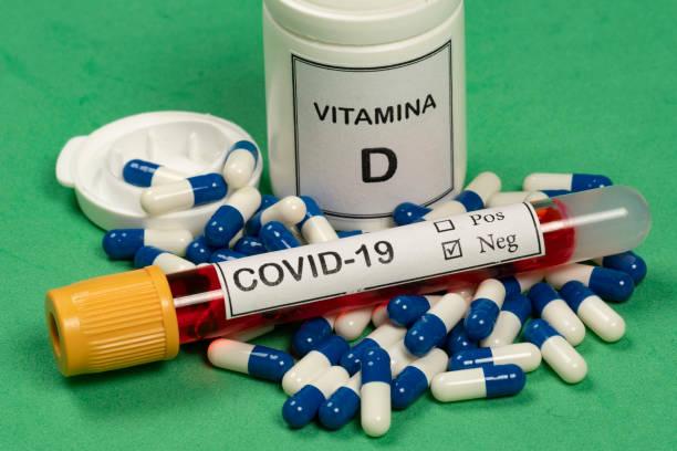 vitamin d container with capsules around - vitamin d стоковые фото и изображения