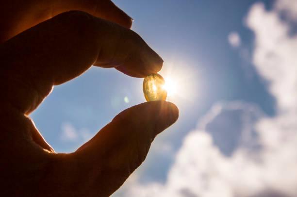la vitamina d mantiene sano mientras que la falta de sol. cápsula de cáscara suave amarillo vitamina d contra el cielo azul y sol en día soleado. concepto de curación. - complemento vitamínico fotografías e imágenes de stock