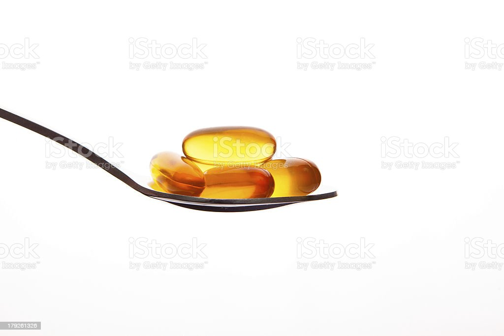 Vitamin fish oil capsule on spoon white background royalty-free stock photo