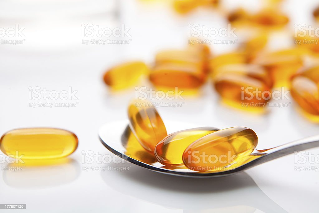 Vitamin fish oil capsule with spoon on white background stock photo