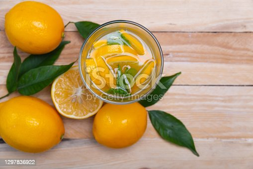 lemon juice in a glass and sliced lemons on a wooden table top view.