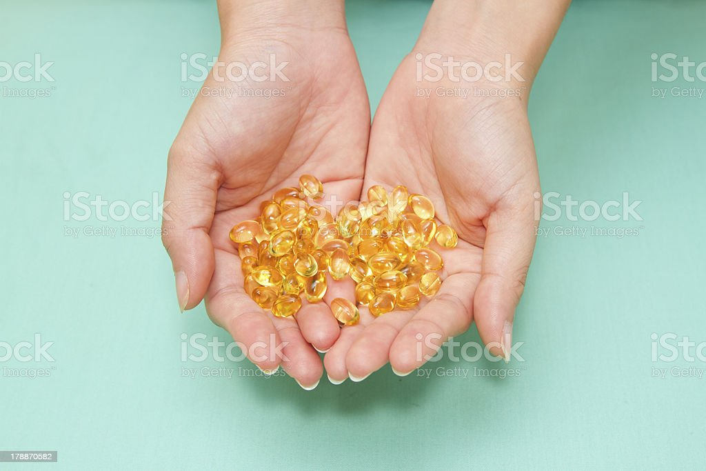 Vitamin Omega-3 fish oil capsules on a hand royalty-free stock photo