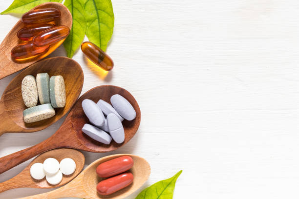 Vitamin pills and capsules Variety of vitamin pills in wooden spoon on white background with green leaf, supplemental and healthcare product, flat lay surface nutritional supplement stock pictures, royalty-free photos & images