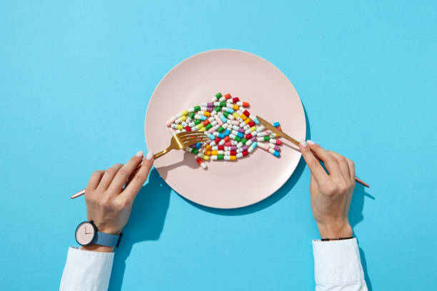 Vitamin pills and tablets in the shape o a fish in a plate and woman's hand with watch on a blue background. Flat lay stock photo