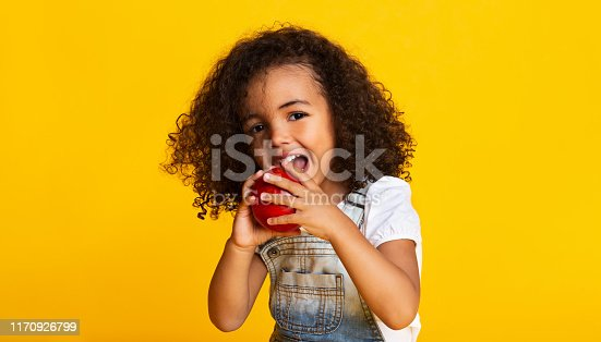 Vitamin snack. Little girl biting red apple over yellow background