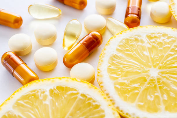 Vitamin supplements and fresh lemon Supplement, Lemon, Vitamins, Nutrition, White Background nutritional supplement stock pictures, royalty-free photos & images