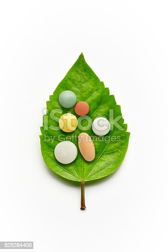 Kinds of vitamins and tablets on a green leaf isolated on a white background.