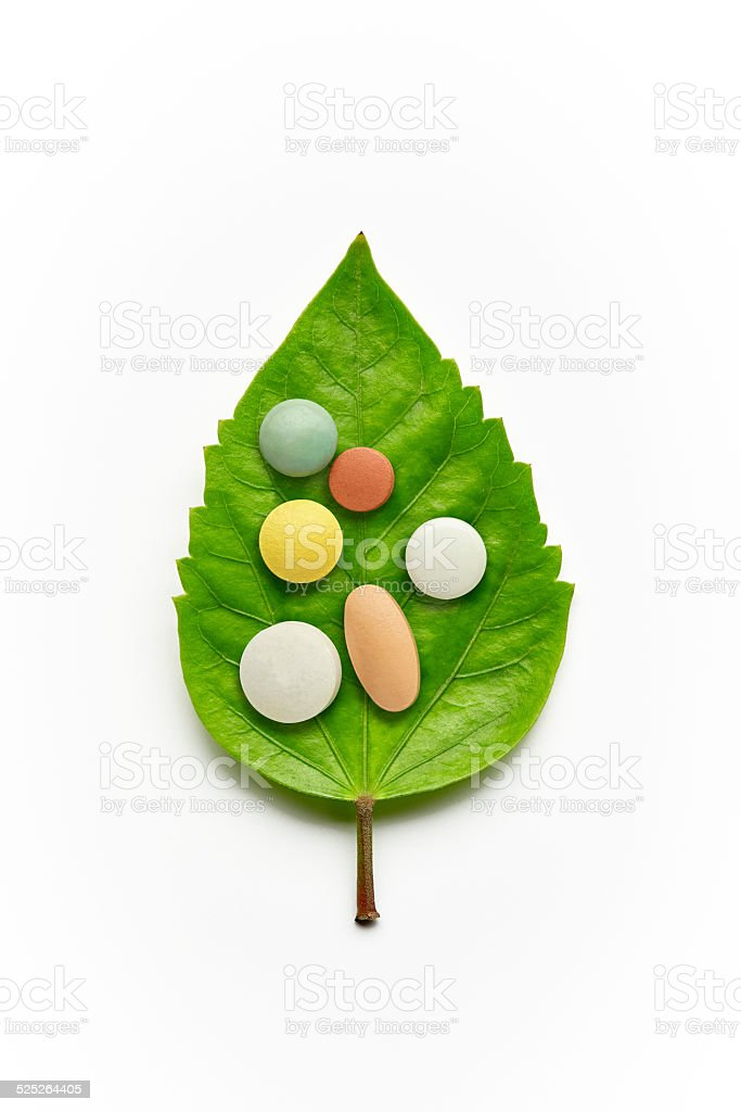 Vitamins and Pills on a Green Leaf stock photo