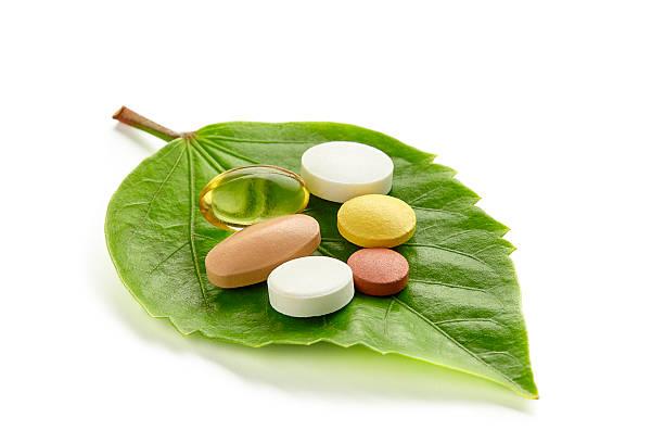 vitamine und tabletten auf einem grünen blatt - nahrungsergänzungsmittel stock-fotos und bilder