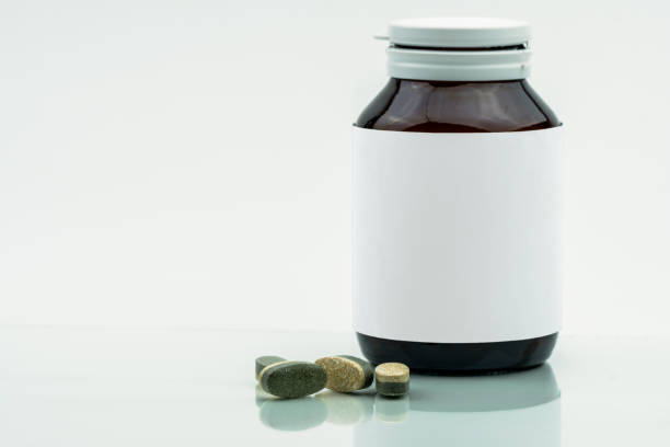Vitamins, supplements and minerals dual layer tablets pills and medicine amber glass bottle with blank label isolated on white background with copy space. Use for vitamins and supplements advertising. stock photo
