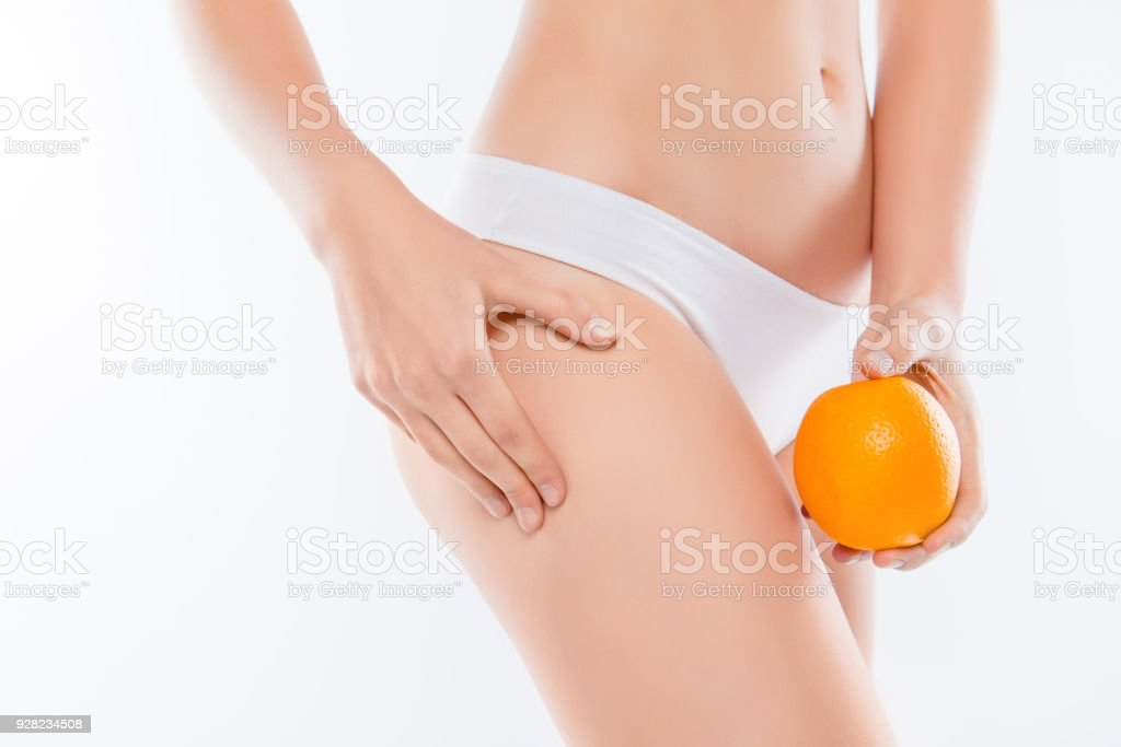 Vitamins vegan lifting sedentary stretch concept. Cropped close up photo of woman's hand holding orange compare showing peel with ideal perfect smooth flawless skin on hips isolated, white background stock photo