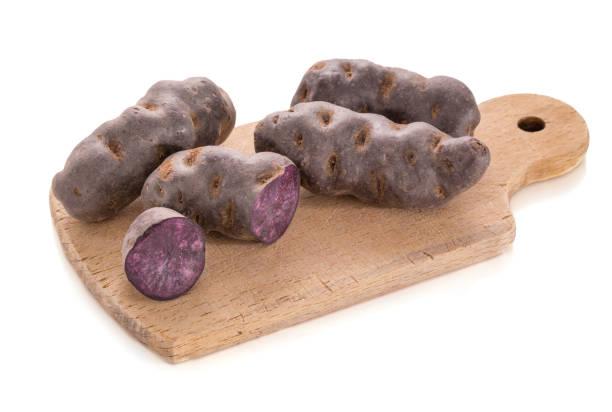 VITELOTTE, lila Kartoffel in Häufchen auf einem Holzbrett – Foto
