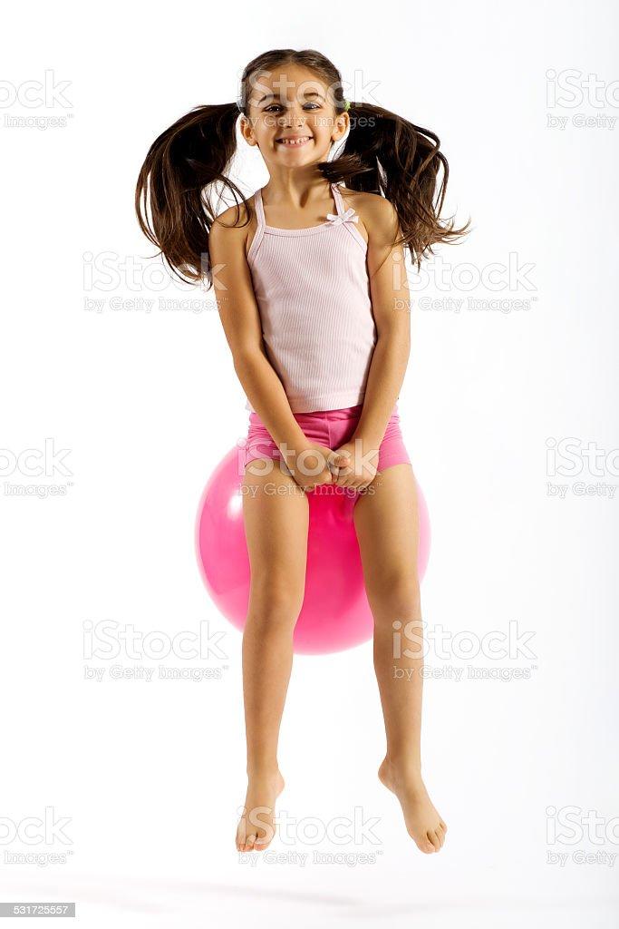 Vivacious little girl on a bouncing ball stock photo