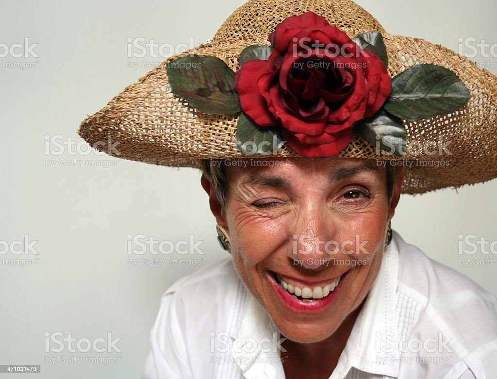 Vivacious Senior Winking at you in a Flamboyant Hat royalty-free stock photo