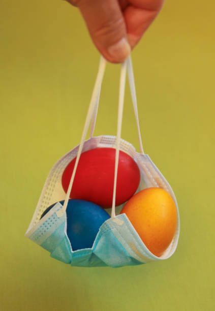Vivid colored eggs in medical mask Easter 2020 stock photo