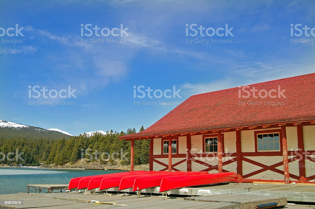 Vivid Colors of Red Canoes and Boathouse stock photo