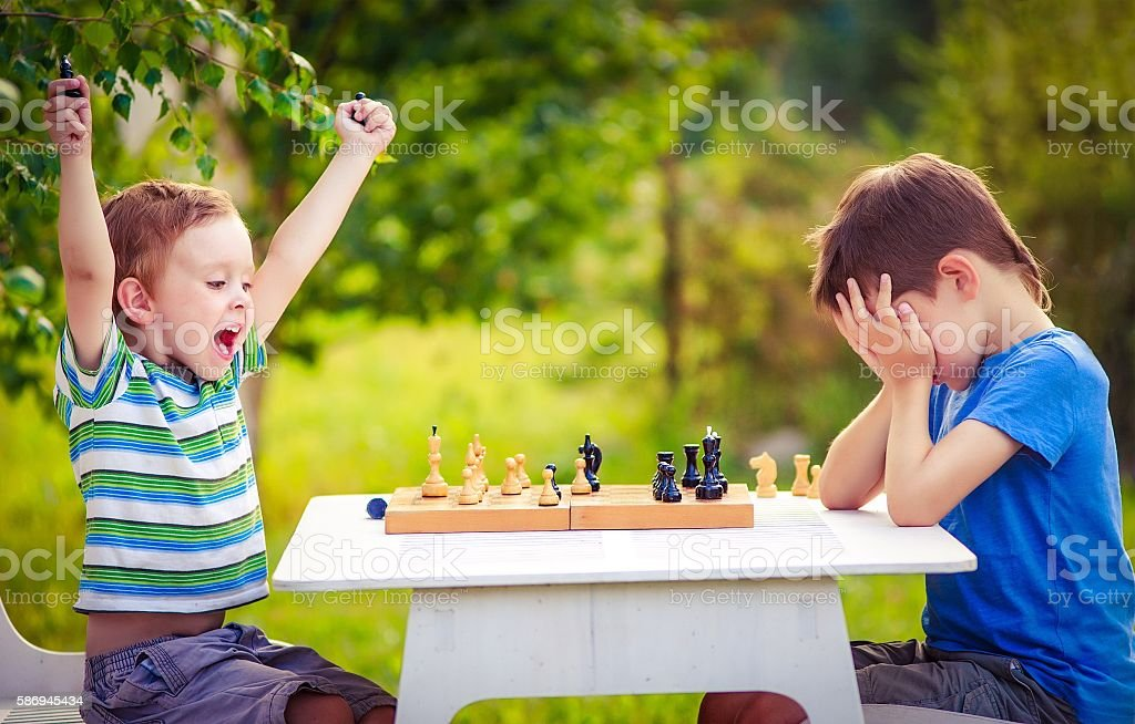 two young chess players outdoors. boy rejoices won a game of chess....
