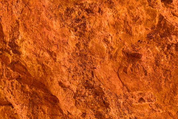 Vivid orange textured background and wallpaper, natural surface of rock formation stock photo