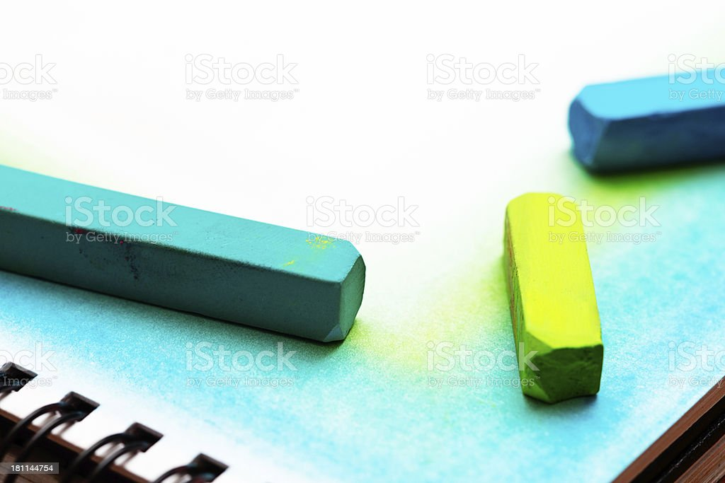Vivid pastel crayons draw blue-green corner on sketchpad royalty-free stock photo
