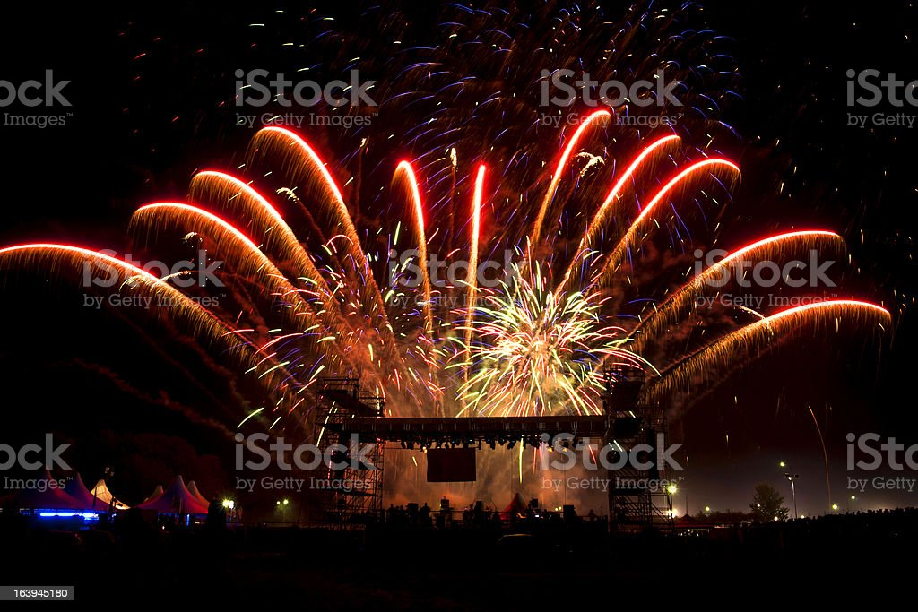 Vivid Red Fireworks Over Stage of New Year's Eve Concert stock photo