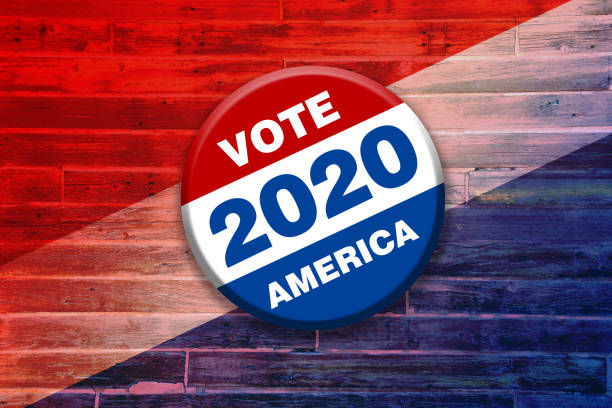 vivid red white blue vote 2020 america button pin on wood background featuring tilted gradient over faded stripes painted over wooden boards used as invitation card sign poster board stock photo