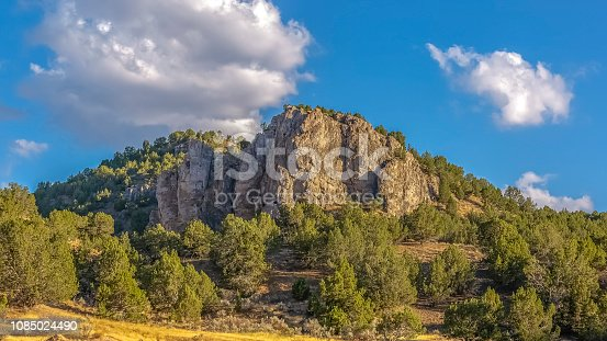 Vivid sky with clouds over Goshen Canyon in Utah. Vivid blue sky with puffy white clouds over the rocky Goshen Canyon in Utah. Rugged landscape with trees and canyon on a sunny day.