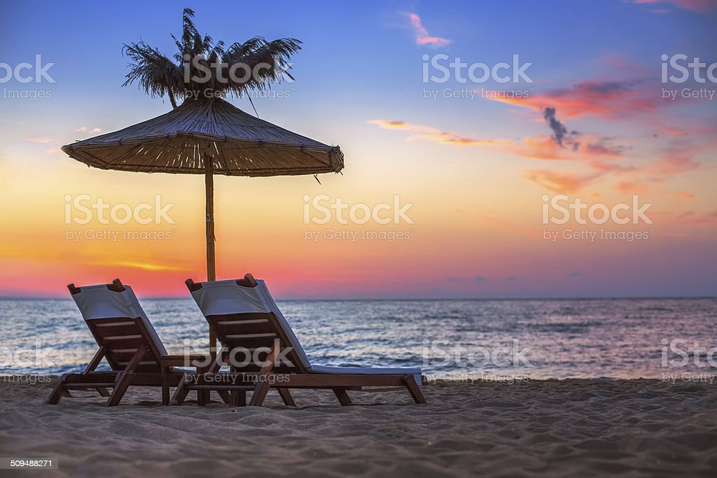 Vivid sunrise on a beautiful sandy beach with sunshade stock photo