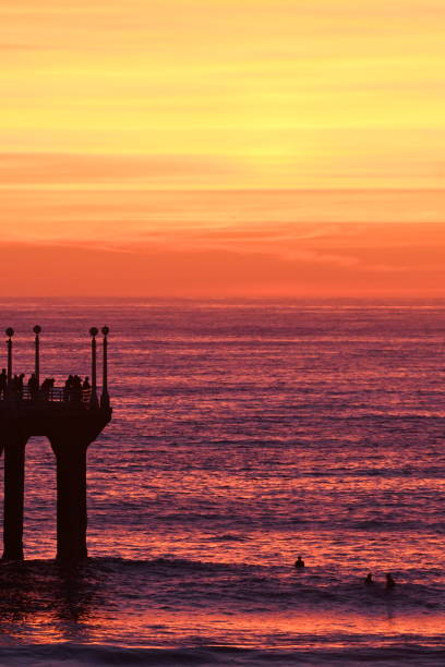 vivid sunset colors with pier and surfers - steven harrie stock pictures, royalty-free photos & images