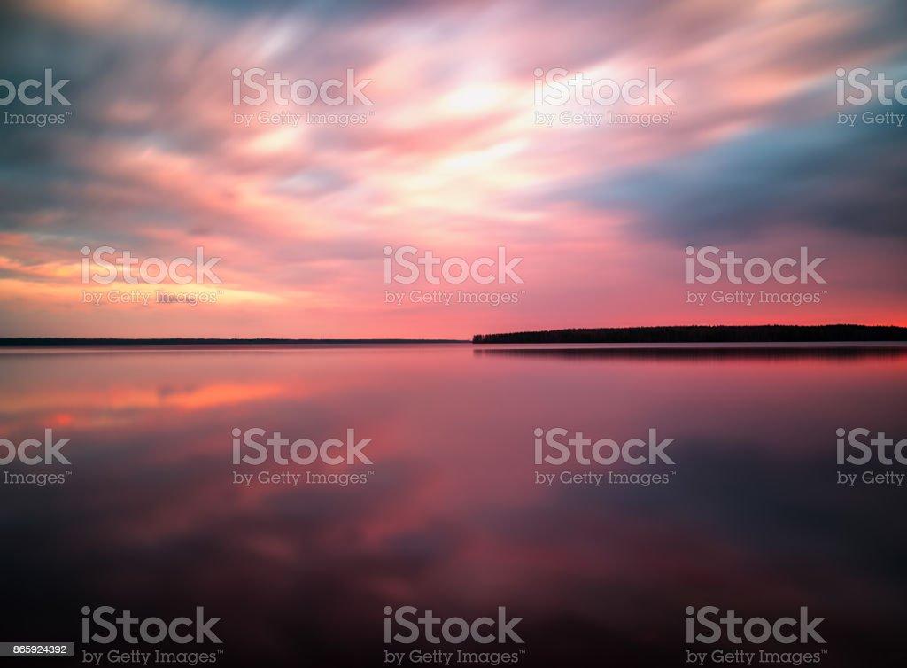 Vivid sunset sunrise horizon lake reflections landscape stock photo